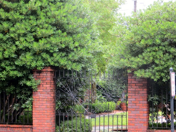 View of one of the secret gardens through black wrought iron gates - downtown
