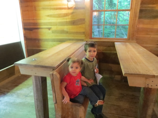 Our Two Grandchildren sitting in the old schoolhouse